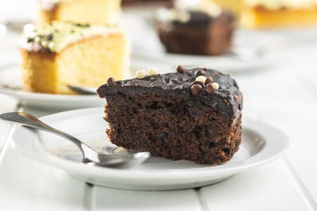 Piece of chocolate cake on dessert plate on white table. Imagens