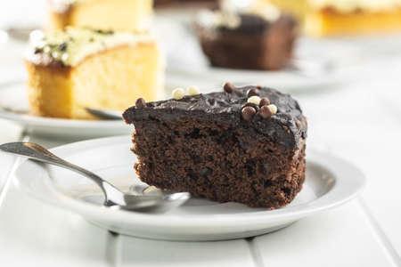 Piece of chocolate cake on dessert plate on white table. 免版税图像