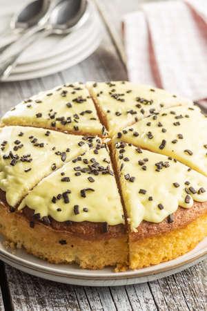 Sweet lemon cake on old wooden table. 免版税图像