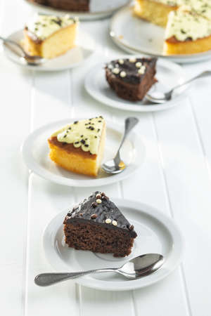 Piece of chocolate and lemon cake on dessert plate on white table.