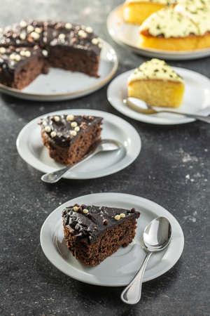 Piece of chocolate cake on dessert plate on black table.