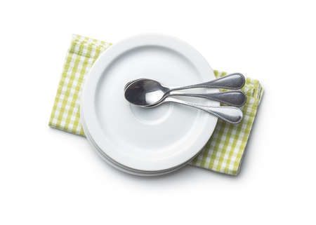 Dessert plates and spoons on checkered napkin isolated on white background.