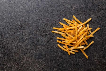 French fries. Fried mini potato sticks on black table. Top view. Imagens