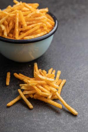 French fries. Fried mini potato sticks on black table.