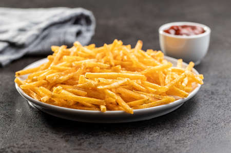 French fries on plate. Fried mini potato sticks on black table.