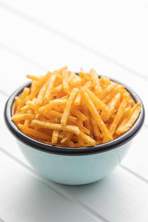 French fries. Fried mini potato sticks in bowl on white table.
