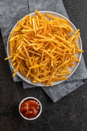 French fries. Fried mini potato sticks and ketchup on black table. Top view. 免版税图像