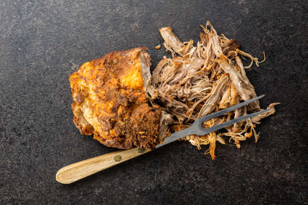 Pulled pork meat with fork on black table. Top view.