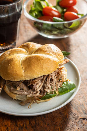 Sandwich with pulled meat on plate on wooden table.