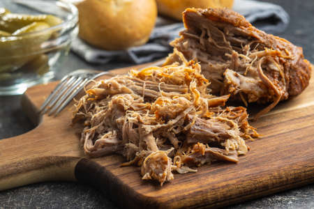 Pulled pork meat on cutting board.