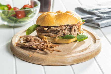 Sandwich with pulled meat on cutting board.