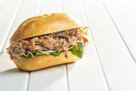Sandwich with pulled meat on white table.