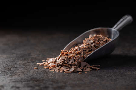 Grated dark chocolate. Chocolate flakes in scoop on black table.