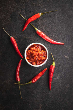 Red hot chili paste and chili pepper in bowl on black table. Top view.
