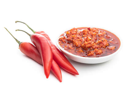 Red hot chili paste in bowl and chili peppers isolated on white background. 版權商用圖片