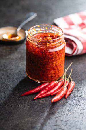 Red hot chili paste and chili pepper in jar on black table. 版權商用圖片