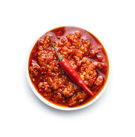 Red hot chili paste in bowl isolated on white background.