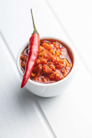 Red hot chili paste and chili pepper on white table. 版權商用圖片