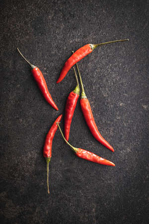 Red chili peppers on black table. Top view.