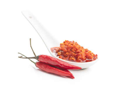 Red hot chili paste in ceramic spoon isolated on white background. 版權商用圖片