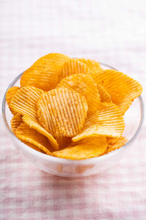 Crispy potato chips in bowl on pink checkered tablecloth. 版權商用圖片 - 161648244