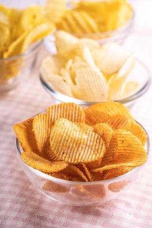 Crispy potato chips in bowl on pink checkered tablecloth. 版權商用圖片 - 161648245