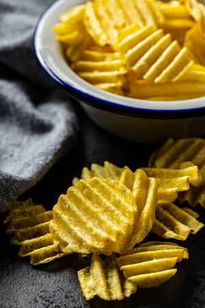 Crispy potato chips on black table.