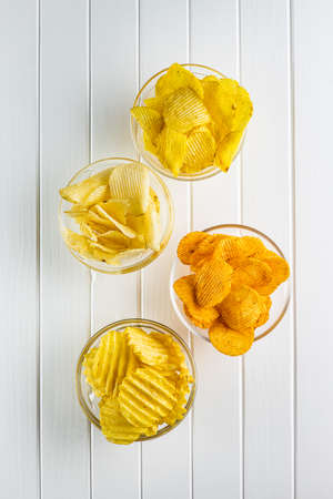 Crispy potato chips with various taste in bowl. Top view.