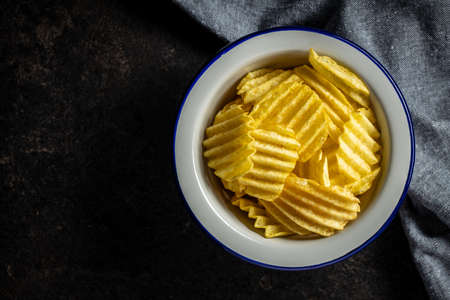 Crispy potato chips in bowl on black table. Top view.