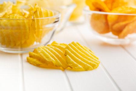 Crispy potato chips on white table.