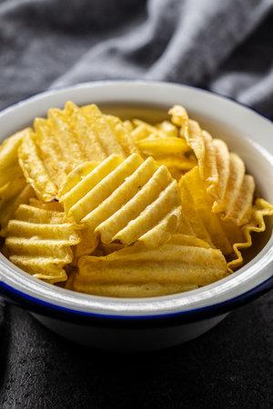 Crispy potato chips in bowl on black table. 版權商用圖片