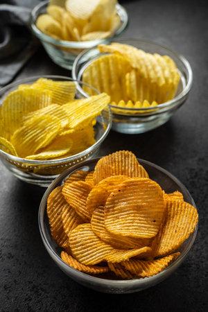 Crispy potato chips with various taste in bowl.