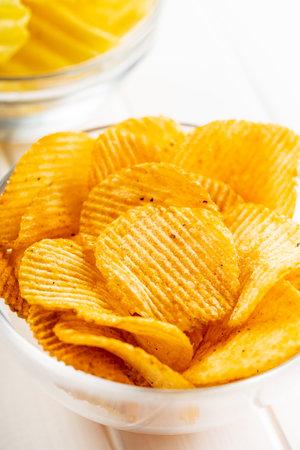 Crispy potato chips in bowl on white table. 版權商用圖片