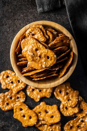 Salted mini flat pretzels in bowl on black table.