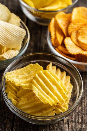Crispy potato chips in bowl on wooden table. 版權商用圖片 - 161695408
