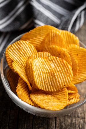 Crispy potato chips in bowl on wooden table. 版權商用圖片 - 161695412