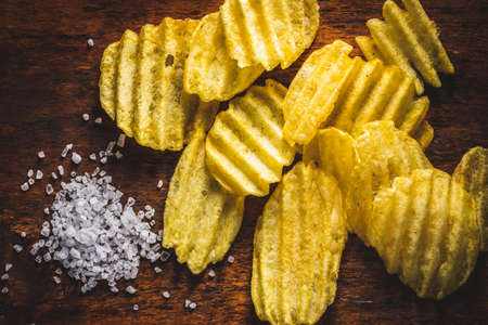 Crispy potato chips and salt on wooden table. Top view.