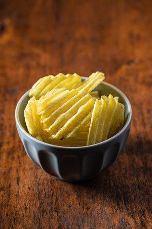 Crispy potato chips in bowl on wooden table. 版權商用圖片