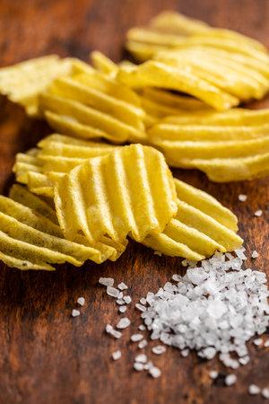 Crispy potato chips and salt on wooden table. 版權商用圖片 - 161695422