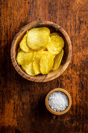 Crispy potato chips in bowl on wooden table. Top view. 版權商用圖片