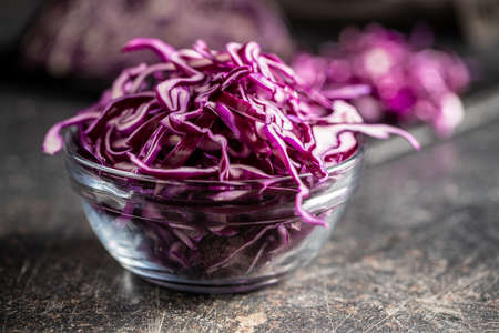 Sliced fresh red cabbage in bowl on black table.