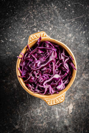 Sliced fresh red cabbage in bowl on black table. Top view.