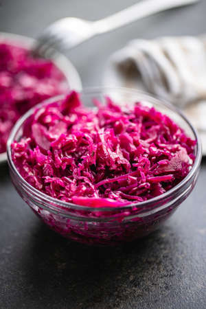 Red sauerkraut. Sour pickled cabbage in bowl on black table.