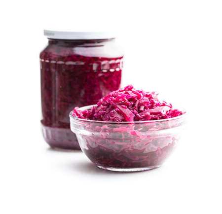Red sauerkraut. Sour pickled cabbage in bowl isolated on white background.
