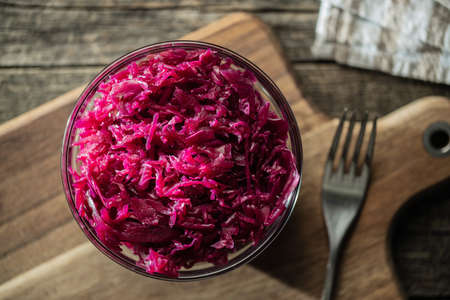 Red sauerkraut. Sour pickled cabbage in bowl on cutting board. Top view.
