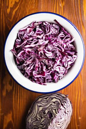 Sliced fresh red cabbage in bowl on wooden table. Top view. 版權商用圖片