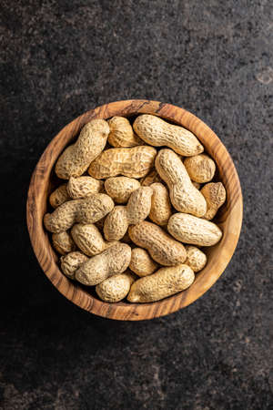 Dried peanuts. Tasty groundnuts in bowl on black table. Top view.