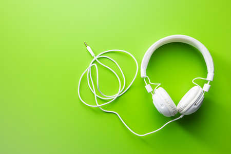 White wired stereo headphones on green background. Top view. Stockfoto - 168154727