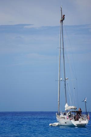 sailingboat: 09.20.2013 Beach Mirtos, Kefalonia,Greece. Man on pole of sailingboat near of beach Mirtos correcting sail Editorial