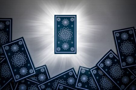 Blue tarot cards scattered on white wood, with a card in the center that gives off light. Supernatural concept